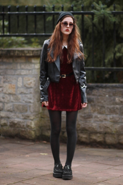 With black leather jacket, hat, black tights and platform shoes