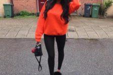 With black leggings, orange sweatshirt and small bag