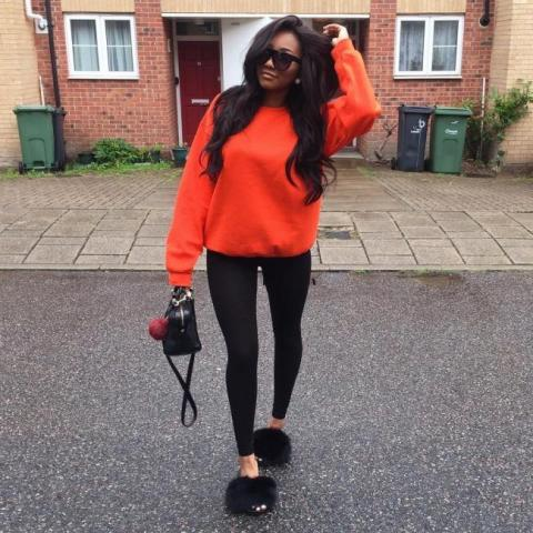 With black leggings, orange sweatshirt and small bag