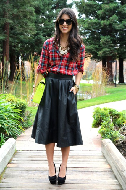 With black midi skirt, green clutch and black platform shoes