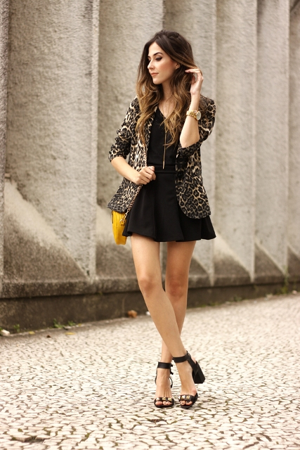 With black mini dress, yellow bag and ankle strap shoes