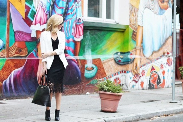 With black shirt, white blazer, black bag and ankle boots