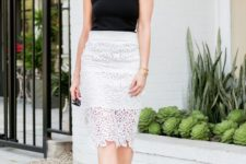 With black sleeveless shirt and white pumps