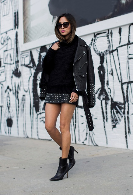 With black sweater, leather jacket and ankle boots