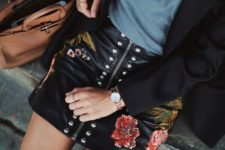 With blue shirt, black blazer and brown bag