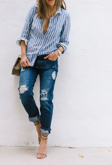 With distressed jeans, small bag and high heels