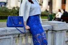 With gray crop shirt, striped jacket, blue bag and beige shoes