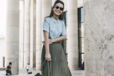 With light blue button down shirt, olive green pleated skirt and embellished bag
