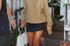 With light brown sweatshirt, white bag and black mini skirt