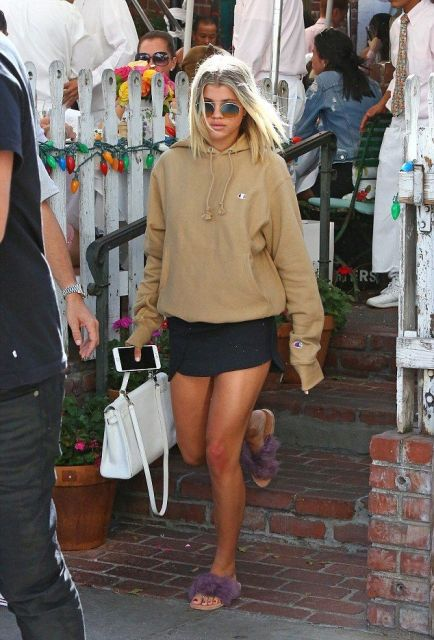 With light brown sweatshirt, white bag and black mini skirt
