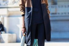 With navy blue shirt, cuffed trousers and brown and navy blue coat
