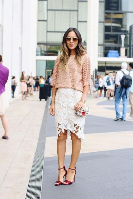 With peach loose sweater, small bag and red high heels