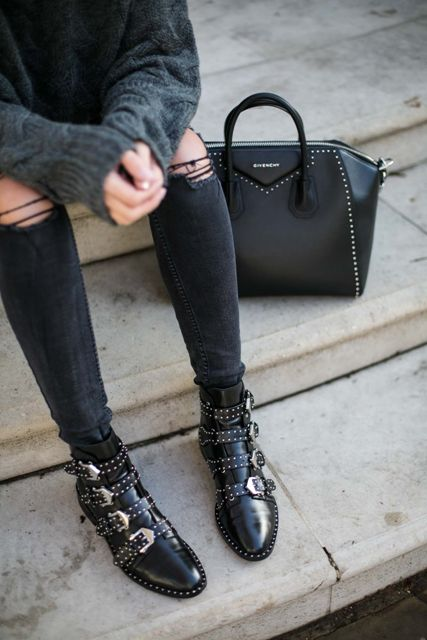 With sweater, distressed pants and black bag