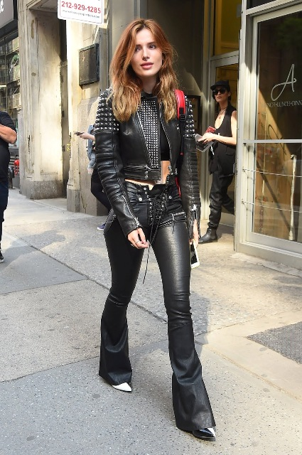 With top, leather flare trousers and high heels