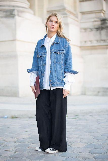 With white loose button down shirt, clutch, wide leg trousers and sneakers