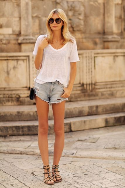 With white loose t shirt, denim shorts and black chain strap bag