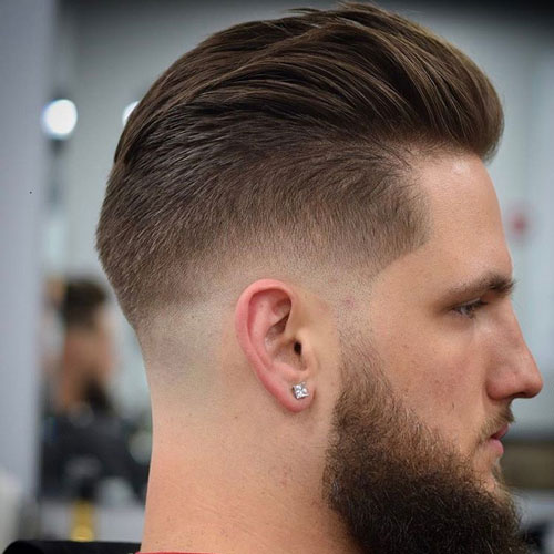 a low bald fade with slicked back hair with beard adds contrast and looks chic
