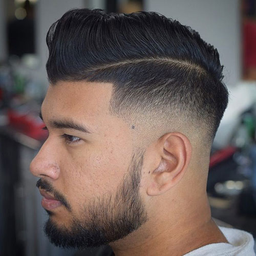 a low razor fade with hard part comb over and a beard is a bold and eye-catchy idea