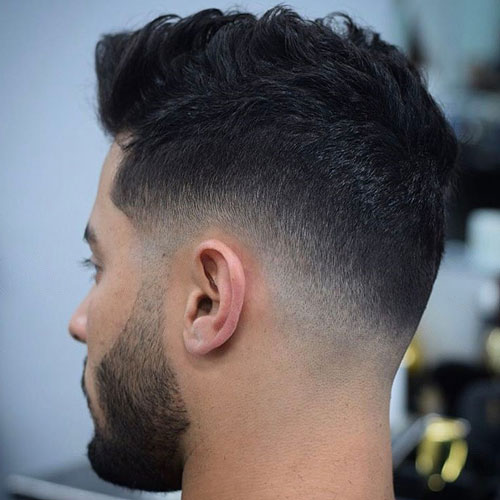 a low skin fade with a messy top is a simple and cute idea for thick hair