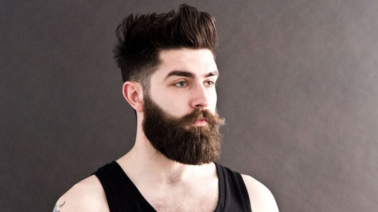 a messy pompadour with low fade is a structural haircut and a beard adds hispter chic