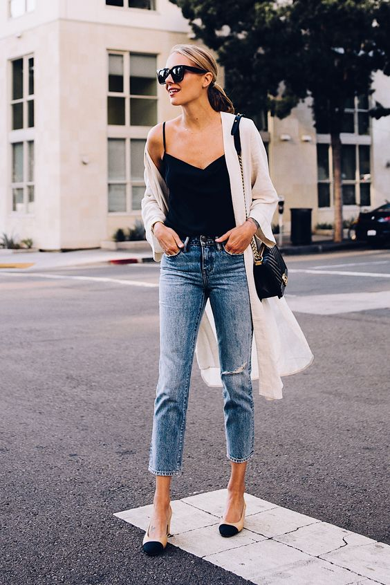 a black spaghetti strap top, blue cropped jeans, a white duster, nude and black slingbacks