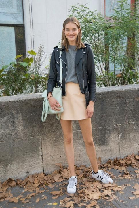 a grey tee, a peachy mini skirt, a black leather jacket, white sneakers and a mint bag