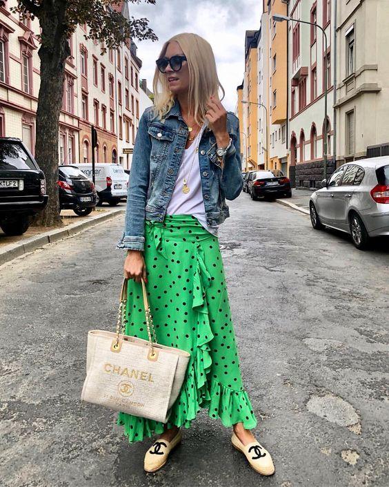 a white tee, a green midi ruffle skirt, a denim jackets, neutral loafers and a neutral bag