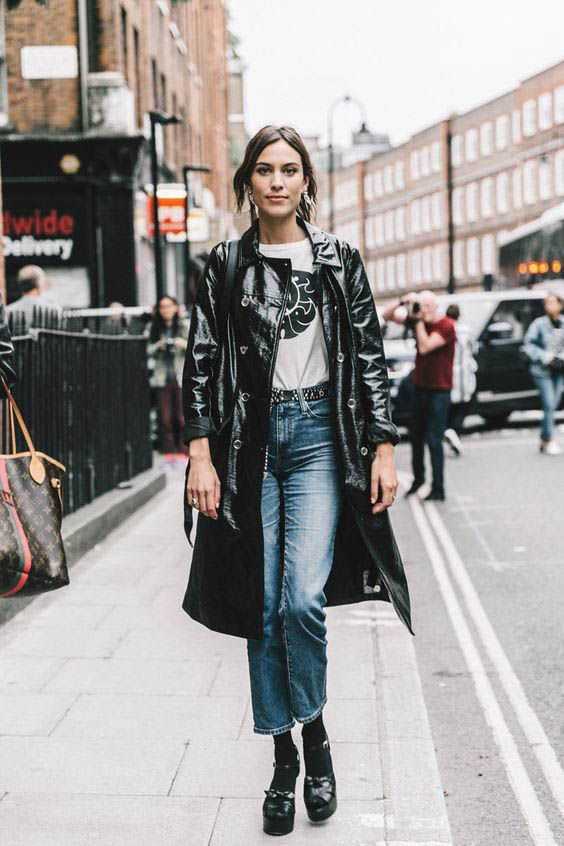 blue jeans, a printed tee, black platform shoes and a black leather trench