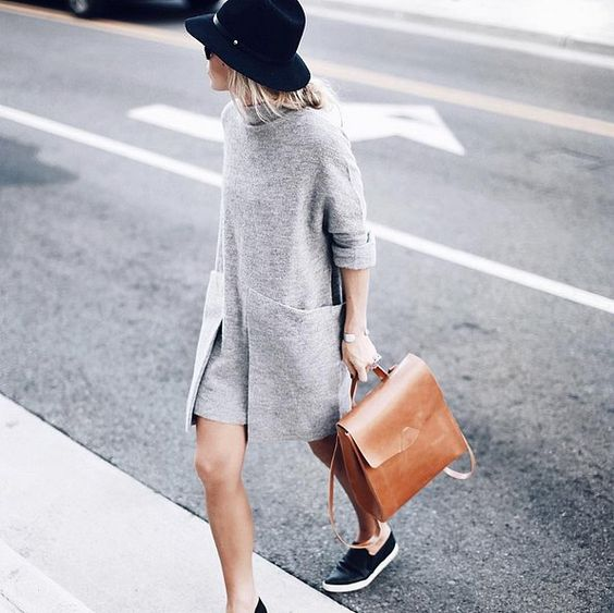 a grey modern over the knee dress, black slipons, a black hat and an amber leather backpack