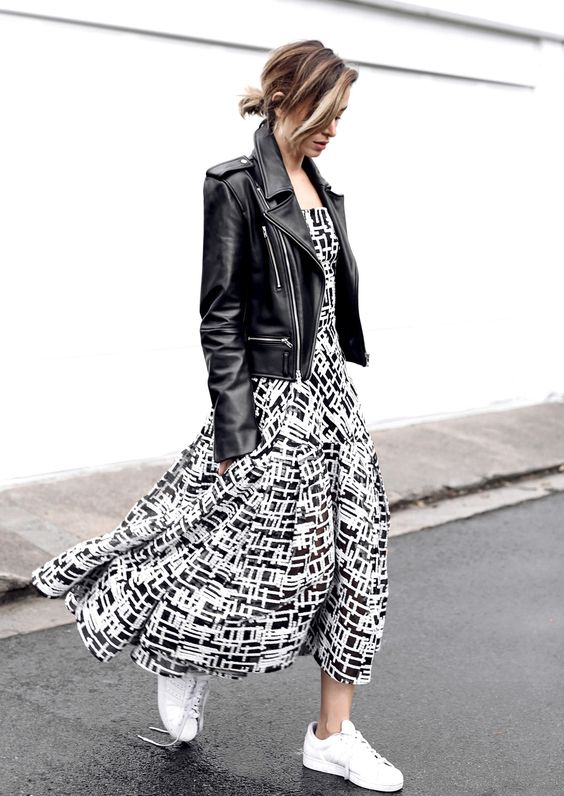 a monochromatic outfit with a black and white midi dress, a black leather jacket, white sneakers