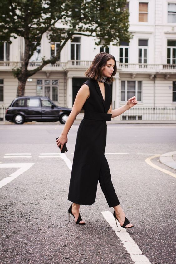 a black jumpsuit with a skirt over it, a tiny black clutch and black heels