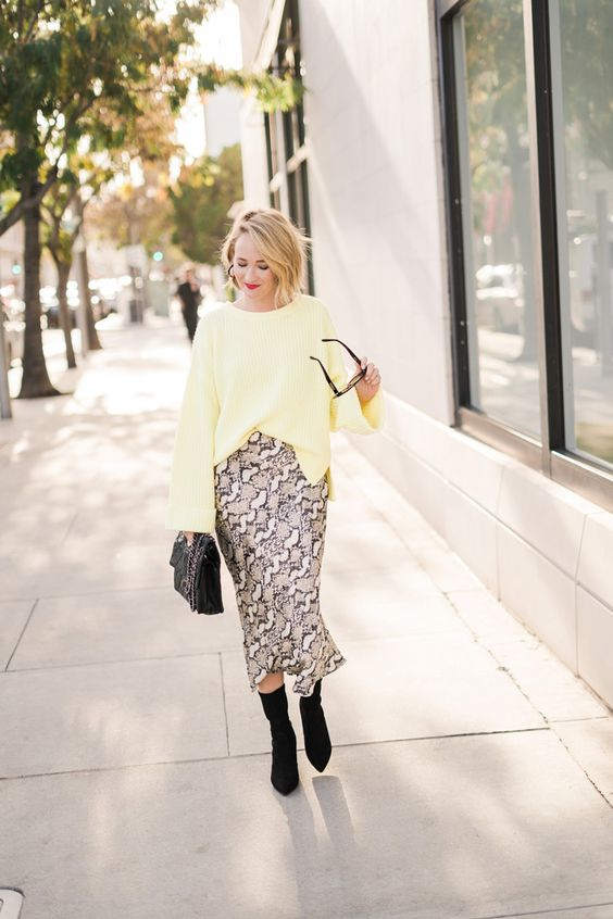 a snake print midi, a yellow top with bell sleeves, black sock boots and a black bag