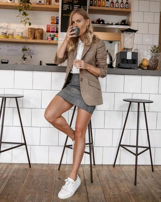 a white shirt, a camel blazer, a grey mini and white sneakers for a casual work outfit