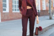 05 a burgundy pantsuit with a matching twisted crop top, silver shoes and a fun bag
