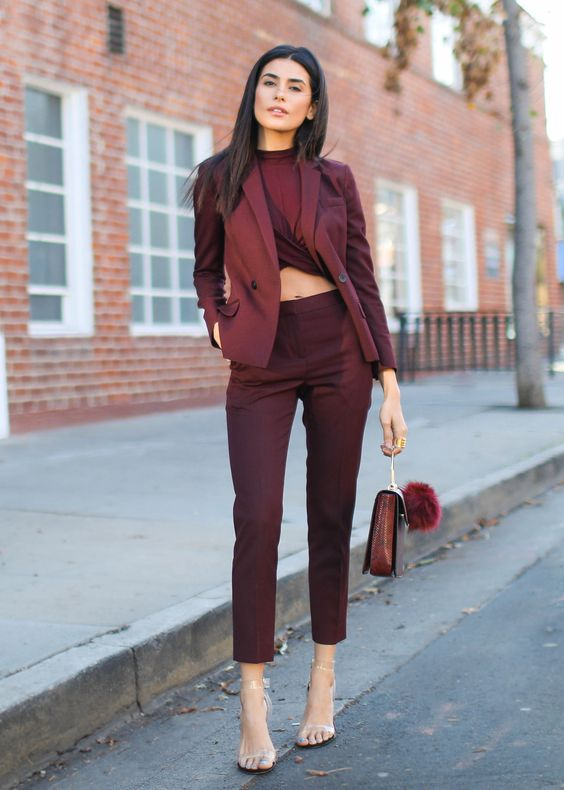 a burgundy pantsuit with a matching twisted crop top, silver shoes and a fun bag