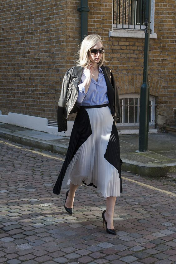 a geometric pleated midi, a blue shirt, black heels and a black leather jacket