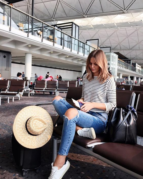 a striped top, blue ripped jeans, white sneakers and a hat for a relaxed casual look