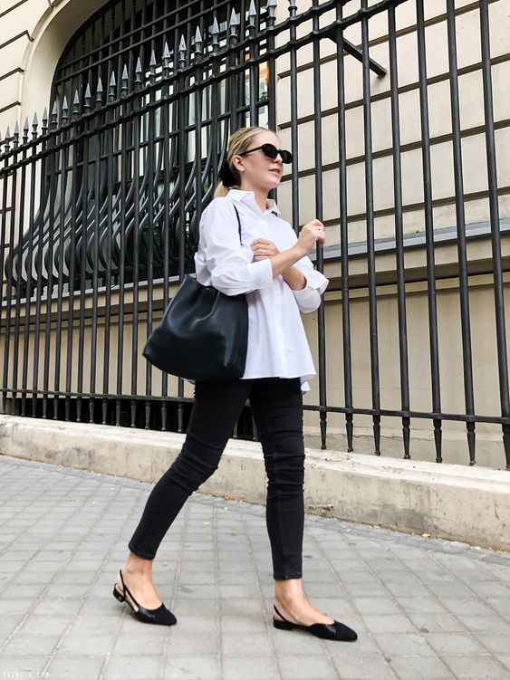 a white shirt, black skinnies, a black comfy bag and black flat slingbacks