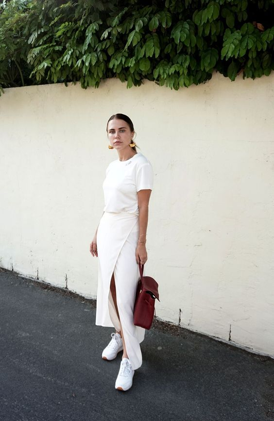 a white tee, a wrap maxi skirt, white sneakers and a brown backpack plus statement earrings