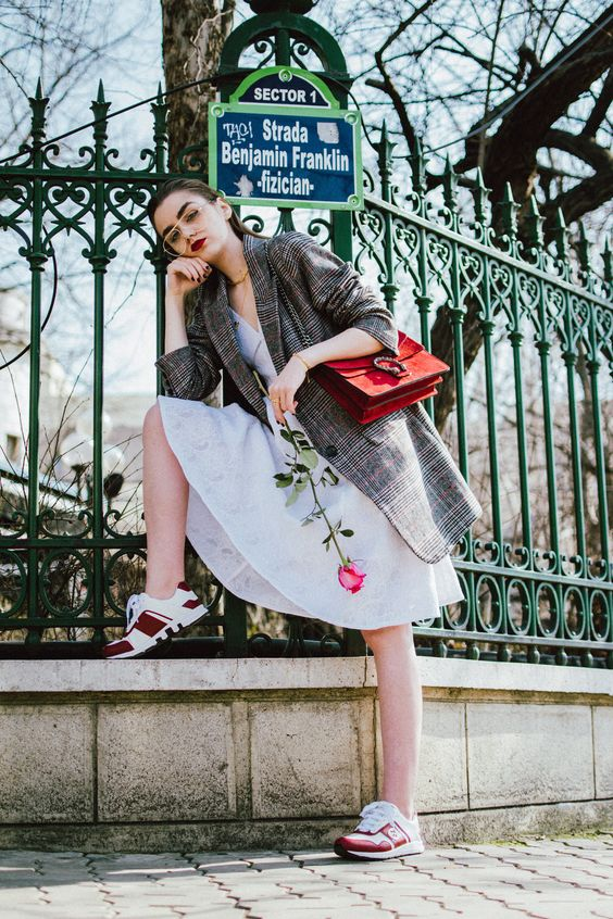an airy white lace dress, an oversized checked blazer, red trainers and a red bag
