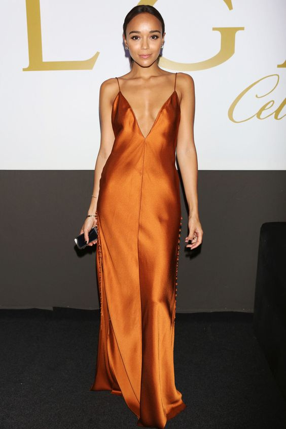 an amber slip maxi dress wit buttons and a plunging neckline, a tiny clutch and statement earrings
