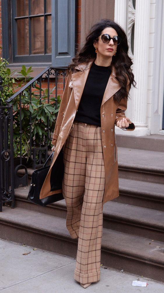 checked wideleg pants, a black top, nude shoes and a brown leather trench by Amal Clooney