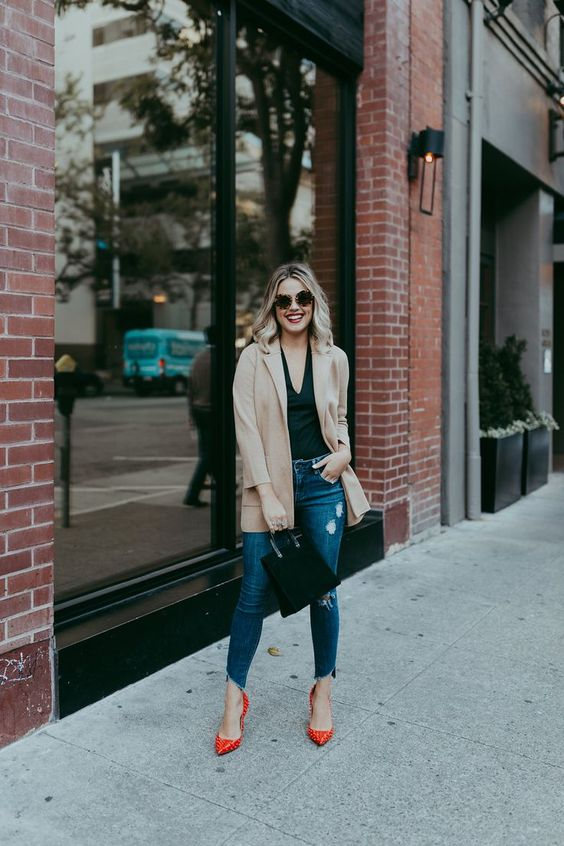a black top, a nude oversized blazer, blue ripped jeans and red spiked shoes