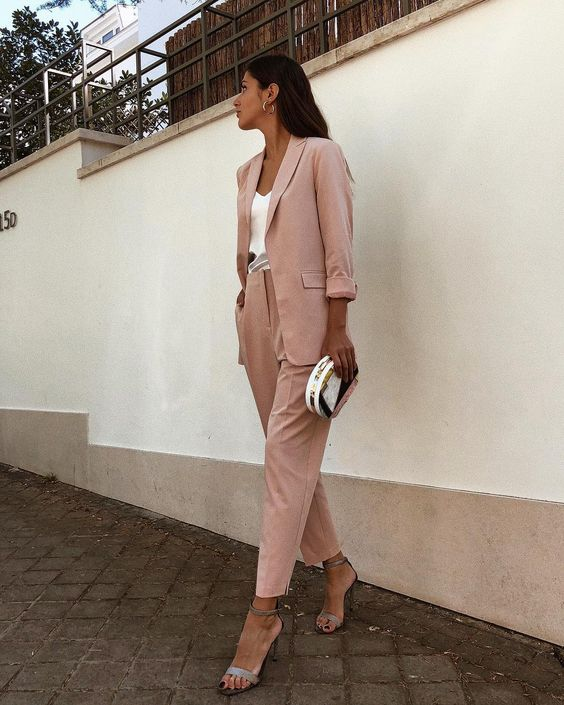 a blush pantsuit with an oversized blazer, a white top, silver shoes and a small clutch