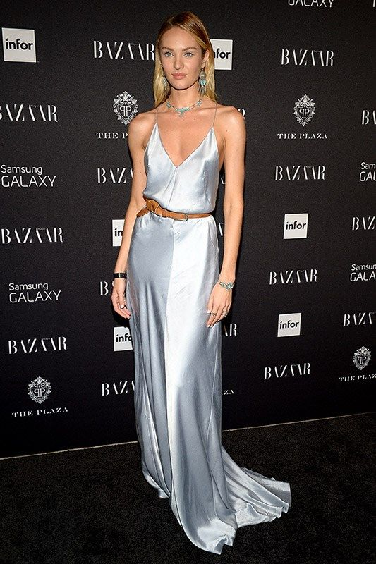 a silver slip maxi dress with a train, a statement necklace and earrings and a belt accent on the waist