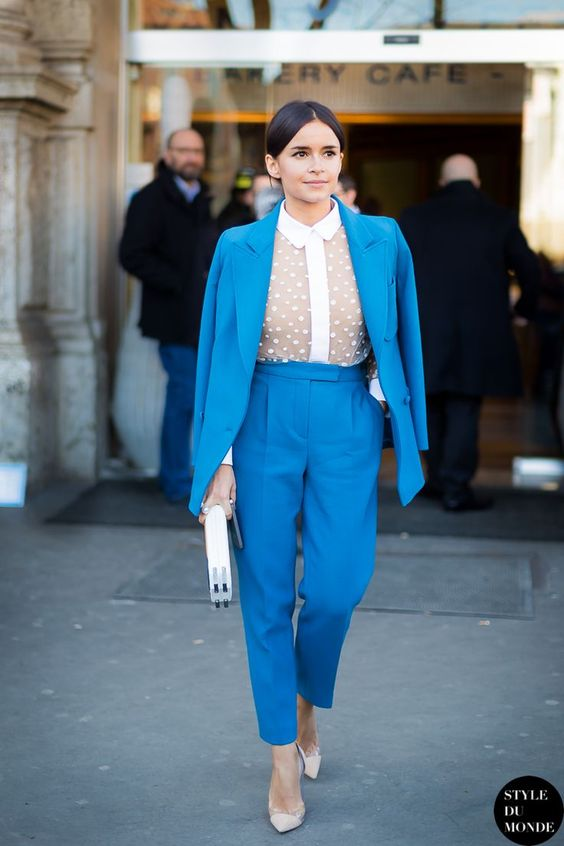 a sky blue pantsuit with cropped pants, a nude polka dot blouse with a white collar, creamy shoes and a white clutch