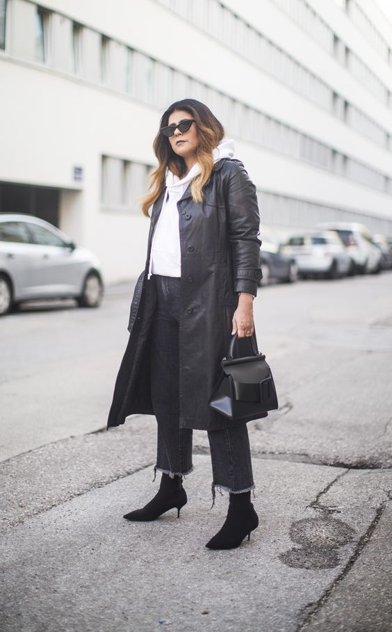black denim, black sock boots, a white hoodie, a black leather trench and a black bag