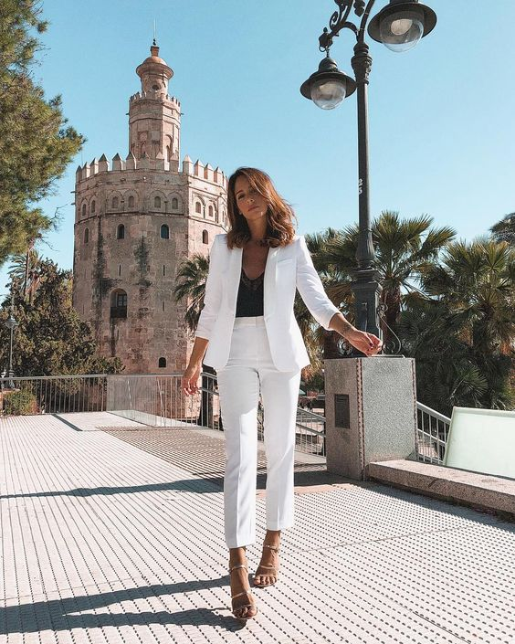 a chic white pantsuit with a black lace top, metallic strappy shoes and a bracelet