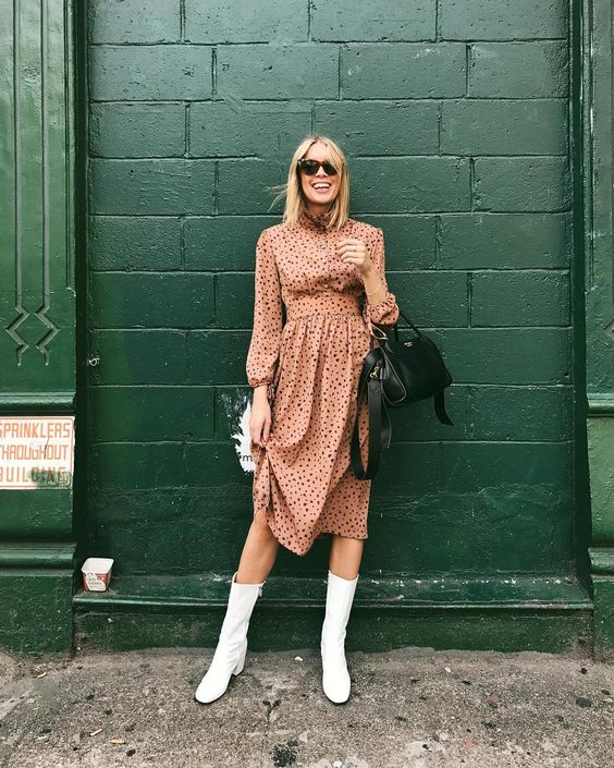 a pink polka dot midi dress, a black bag and white tall boots for an effortlessly girlish look