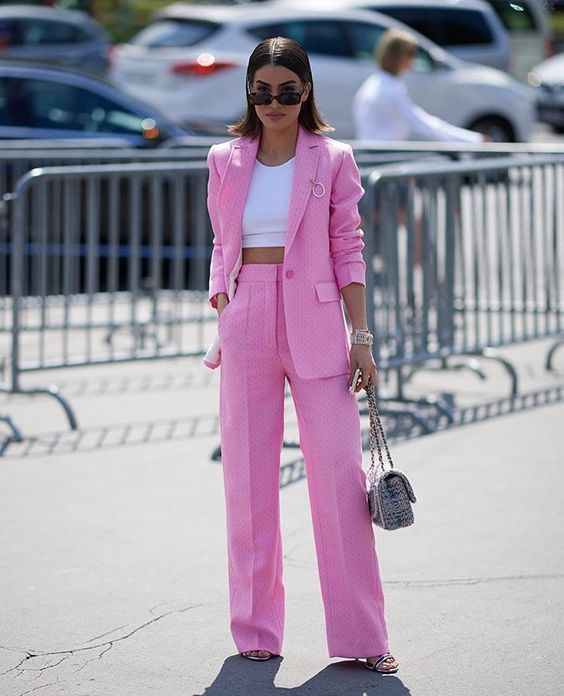 a pink polka dot pantsuit, a white crop top, silver shoes and a printed bag